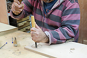 A man engraving a block of wood with a mallet and chisel