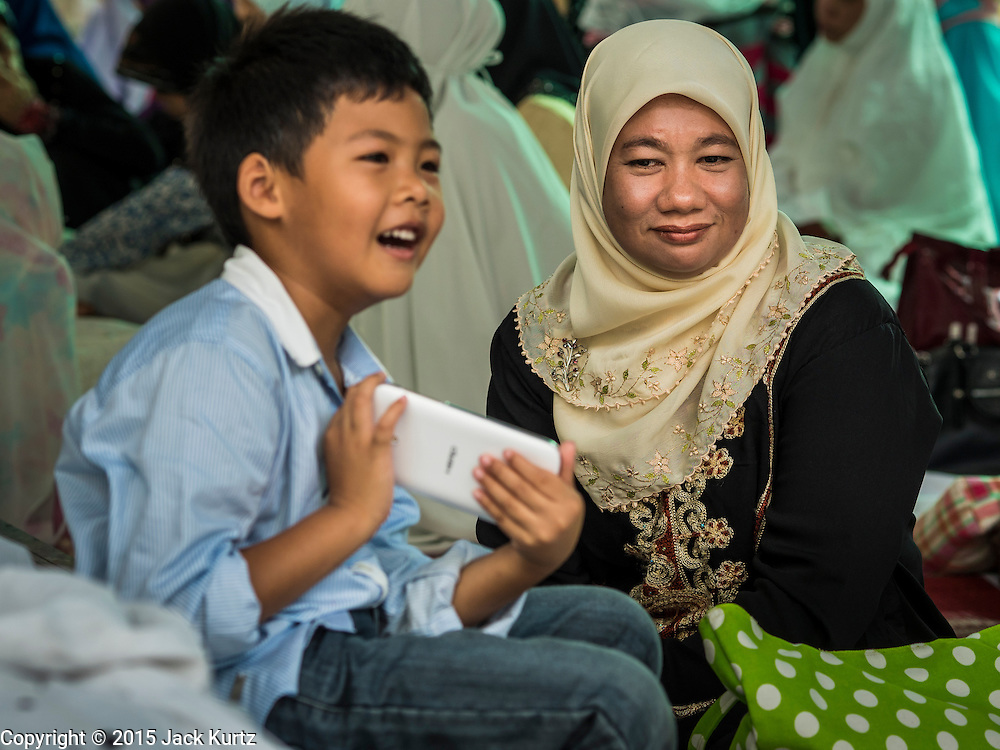 17 JULY 2015 - BANGKOK, THAILAND:     A woman talks to her son during Eid al-Fitr services at Ton Son Mosque in Bangkok. Eid al-Fitr is also called Feast of Breaking the Fast, the Sugar Feast, Bayram (Bajram), the Sweet Festival or Hari Raya Puasa and the Lesser Eid. It is an important Muslim religious holiday that marks the end of Ramadan, the Islamic holy month of fasting. Muslims are not allowed to fast on Eid. The holiday celebrates the conclusion of the 29 or 30 days of dawn-to-sunset fasting Muslims do during the month of Ramadan. Islam is the second largest religion in Thailand. Government sources say about 5% of Thais are Muslim, many in the Muslim community say the number is closer to 10%.          PHOTO BY JACK KURTZ