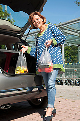 Senior woman stowing vegetable and fruit in car trunk