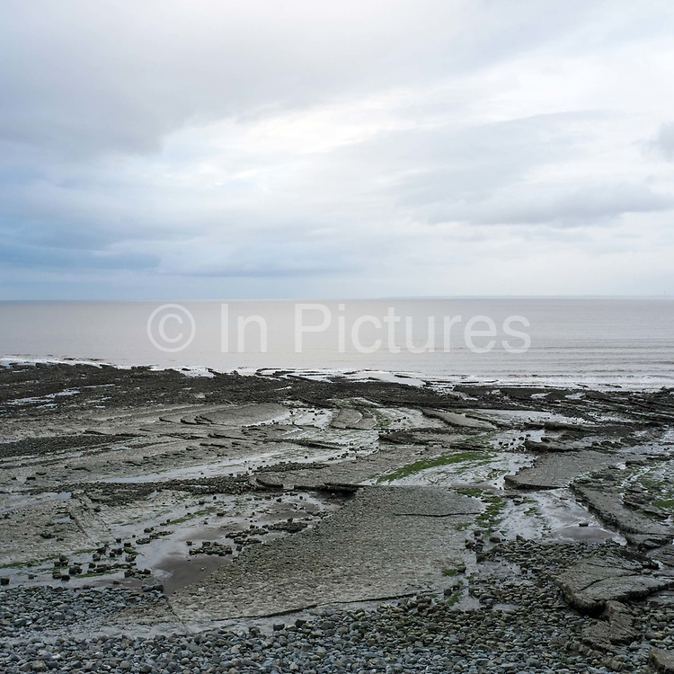A view of the beach and coastline at East Quantoxhead on 14th March 2020 in Somerset, United Kingdom. This pebble, rock and sand beach which has many interesting rock formations sits on the Somerset coast, where the Quantock Hills meet the sea. This stretch of the coast features tall Jurassic cliffs and many interesting fossils can be found here, including reptile remains and ammonites.