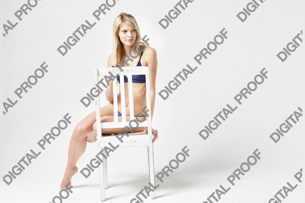 Frontal view of a Girl in bikini sitting over a white chair isolated in studio with a white background with copy space