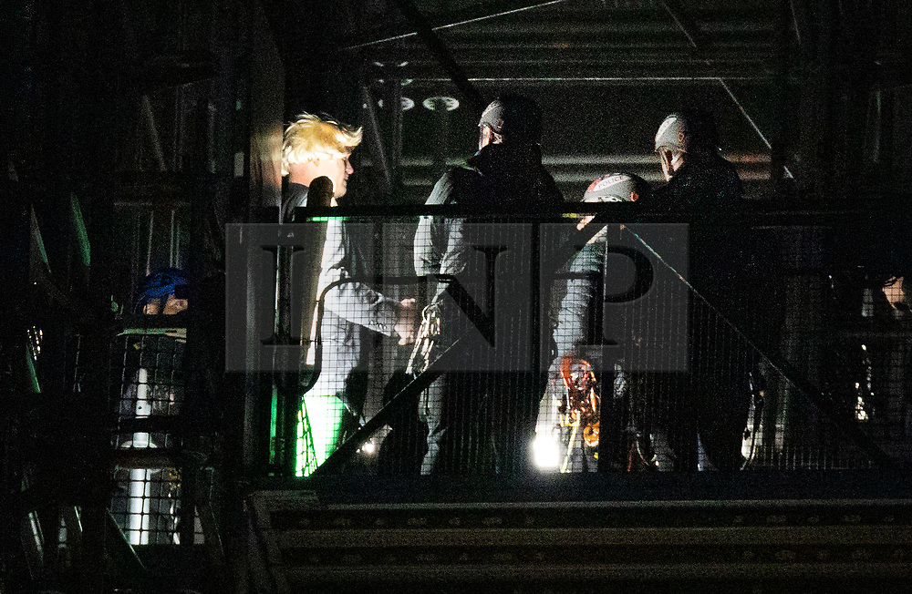 © Licensed to London News Pictures. 18/10/2019. London, UK. Police detain a protester after he scaled the scaffolding surrounding Big Ben. He is believed to be part of an Extinction Rebellion protest. Photo credit: Peter Macdiarmid/LNP