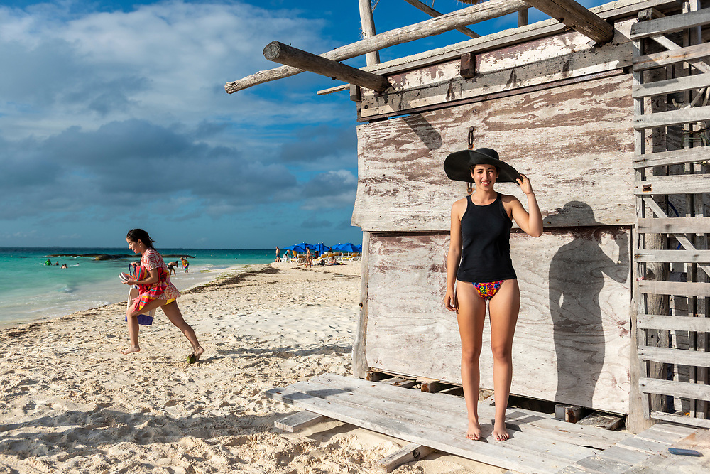 Lucia, from Mexico, enjoying a day of vacation on Isla Mujeres, an island in the Caribbean Sea 13 kilometers off the coast from Cancún. Her friend is seen running on the left. (December 22, 2014)