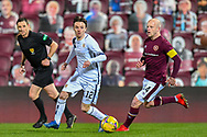 Stefan Scougall (#12) of Alloa Athletic FC cuts inside of Steven Naismith (#14) of Heart of Midlothian FC during the SPFL Championship match between Heart of Midlothian FC and Alloa Athletic FC at Tynecastle Park, Edinburgh, Scotland on 9 April 2021.