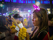 """31 DECEMBER 2012 - BANGKOK, THAILAND: Thais pray for a prosperous New Year on New Year's Eve at the Erawan Shrine in the Ratchaprasong Intersection in Bangkok. Many Thais go to Buddhist temples and shrines to """"make merit"""" for the New Year. The traditional Thai New Year is based on the lunar calender and is celebrated in April, but the Gregorian New Year is celebrated throughout the Kingdom, especially in larger cities and tourist centers, like Bangkok, Chiang Mai and Phuket. The Bangkok Countdown 2013 event was called """"Happiness is all Around @ Ratchaprasong."""" All of the streets leading to Ratchaprasong Intersection were closed and the malls in the area stayed open throughout the evening.    PHOTO BY JACK KURTZ"""