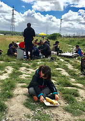 30July2021. Calais, France.<br /> A 6 yr old Kurdish child sits down to eat lunch provided by Care4Calais and other charities offering food, assistance, phone charging, haircuts, clothing, tents and more to migrant refugees in Dunkerque. A new 'Jungle' appears to be springing up from the trees and woods on the outskirts of Dunkerque where conditions are not as hostile or inhospitable as they are currently in Calais 30km to the south.<br /> Photo©; Charlie Varley/varleypix.com