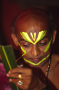 Professor Balasubramanian, a senior teacher of Kathakali applies his make up before a performance at the Kerala Kalamandalam.<br /> The Kalamandalam was founded in 1930 to preserve the cultural traditions of Kathakali, the stylised dance drama of Kerala. Kathakali is the classical dance-drama of Kerala, South India, which dates from the 17th century and is rooted in Hindu mythology. Kathakali is a unique combination of literature, music, painting, acting and dance performed by actors wearing extensive make up and elaborate costume who perform plays which retell in dance form stories from the Hindu epics.
