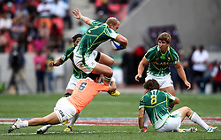 Phillip Snyman of South Africa jumps over Lucas Alcacer of Argentina attempted tackle during the Cup Semi Final between South Africa and Argentina on Day 2 of the HSBC Sevens World Series Port Elizabeth Leg held at the Nelson Mandela Bay Stadium on 8th December 2013 in Port Elizabeth, South Africa. Photo by Shaun Roy/Sportzpics