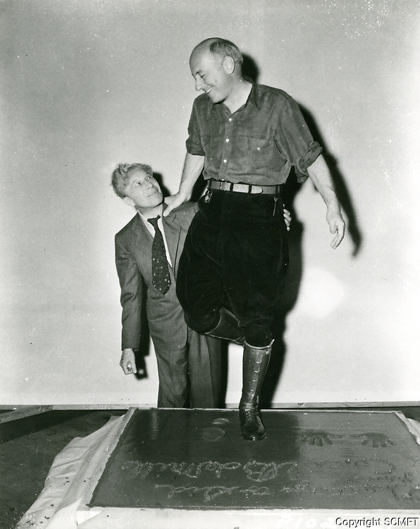 1941 Cecil B DeMille with Sid Grauman at his hand and footprint ceremony at the Chinese Theater