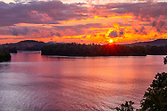 The sun sets over Summersville Lake in West Virginia creating a fiery orange sky reflecting off the gentle summer waters.