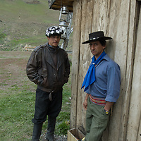 Chilean gauchos stand outside a shed near Torres del Paine National Park in Patagonia, Chile.