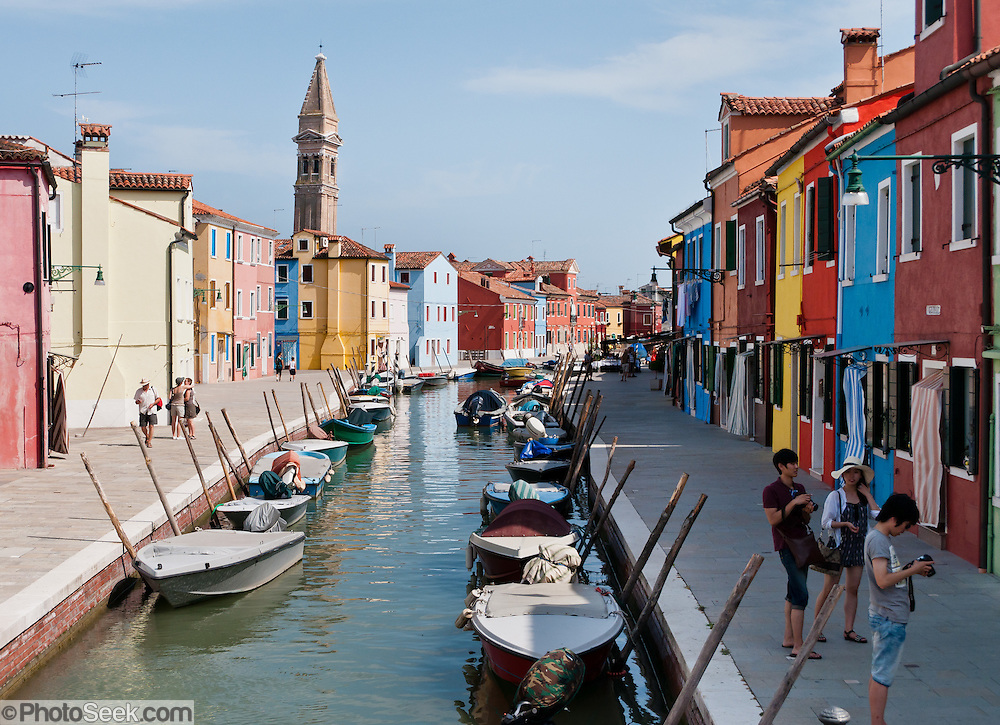 "The tilting campanile (bell tower) of the Church of San Martino contrasts with upright houses in Burano, in the Venetian Lagoon, Italy, Europe. Burano, known for knitted lacework, fishing, and colorfully painted houses, is a small archipelago of four islands linked by bridges in the Venetian Lagoon. Burano's traditional house colors are strictly regulated by government. The Romans may have been first to settle Burano. Romantic Venice (Venezia), ""City of Canals,"" stretches across 100+ small islands in the marshy Venetian Lagoon along the Adriatic Sea in northeast Italy, between the mouths of the Po and Piave Rivers. Venice and the Venetian Lagoon are honored on UNESCO's World Heritage List."