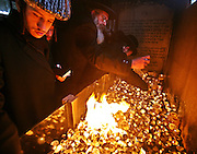 Orthodox Jews from Stamford Hill light candles at the tomb of Rabbi Shulem Moshkovitz, The Shotzer Rebbe who is buried in the Adath Yisroel cemetery, Enfield. Before his death in 1958 (5718 Jewish years) he promised to help everyone who attended his tomb on a Friday morning and lit 3 candles.  It is thought by people in the local community that thousands have had spiritual help after lighting candles and praying here. On Friday the 12th of January 2007 it was the anniversary of his death, hundreds of people turned up to light candles, place them on his tomb and pray.