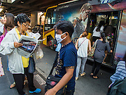 04 FEBRUARY 2015 - BANGKOK, THAILAND: People at a bus stop on Silom Road in Bangkok's financial district. After months of relative calm following the May 2014 coup, tensions are increasing in Bangkok. The military backed junta has threatened to crack down on anyone who opposes the government. Relations with the United States have deteriorated after Daniel Russel, the US Assistant Secretary of State for Asian and Pacific Affairs, said that normalization of relations between Thailand and the US would depend on the restoration of a credible democratically elected government in Thailand.    PHOTO BY JACK KURTZ