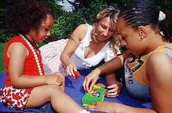 Lesbian couple with young daughter in park,