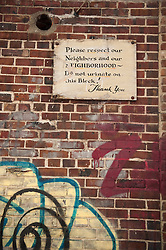 sign on brick wall covered with graffiti