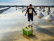 22 FEBRUARY 2017 - BAN LAEM, PETCHABURI, THAILAND: A salt field worker gets a drink of water from a cooler chest during the salt harvest in Petchaburi province of Thailand, about two hours south of Bangkok on the Gulf of Siam. Salt is collected in coastal flats that are flooded with sea water. The water evaporates and leaves the salt in large pans. Coastal provinces south of Bangkok used to be dotted with salt farms, but industrial development has pushed the salt farms down to remote parts of Petchaburi province. The harvest normally starts in early February and lasts until early May, but this year's harvest was delayed by a couple of weeks because of unseasonable rain in January that flooded many of the salt collection ponds.    PHOTO BY JACK KURTZ