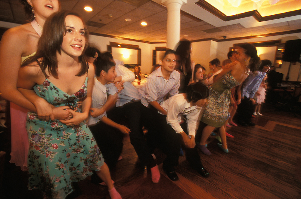 Friends join a Jewish bat mitzvah girl in party games in New Jersey, USA. She belongs to a Reform Jewish synagogue, where Sabbath observance rules are less strict than among Conservative or Orthodox congregations, and her reception is held straight after the synagogue ceremony.
