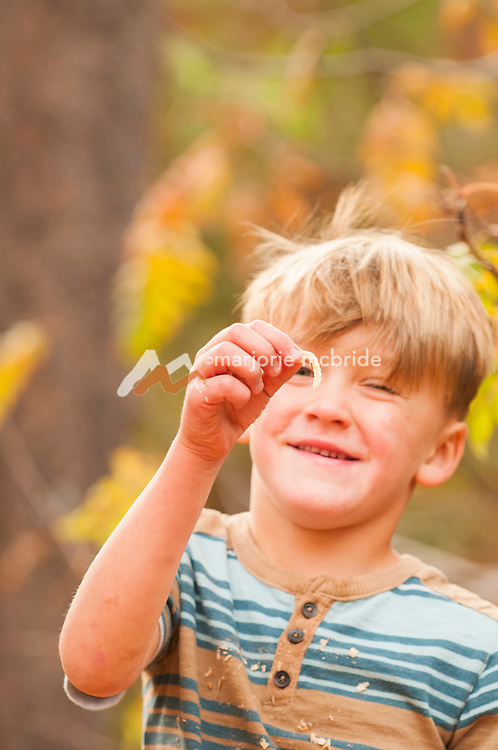 Little boy finds wood worm, McCall, Idaho. MR