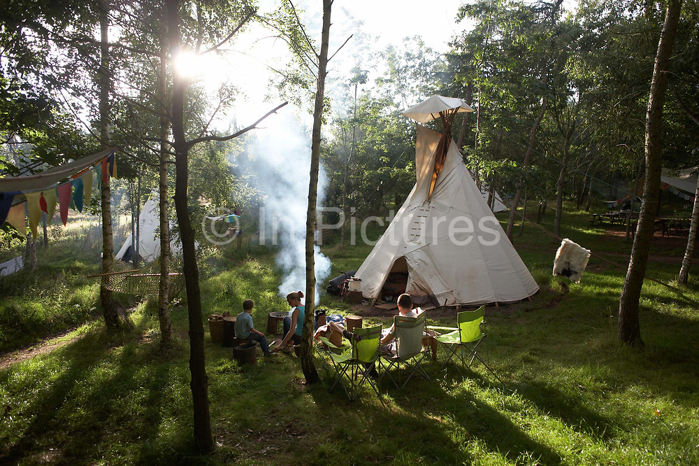 A family relax in late-afternoon sunshine and wood smoke in a quiet field at Woodland Tipi and Yurt Holidays near Little Dewchurch, Herefordshire. We see the sun shining through pine trees and long shadows stretching through the fresh grass where camping seats and a camp-fire is billowing clouds of smoke, just like in the days of cowboys and indians. The holidaymakers are staying in 17 acres of an Area of Outstanding Natural Beauty, experiencing the peace and tranquillity of tipi and yurt camping in their own private, secluded valley - an ever-increasingly popular holiday adventure that is both green and carbon neutral since they are not using electricity for heating or cars to travel. It is also a stress-free lifestyle, away from the pressures of work and urban life, where travellers can unwind safe in the knowledge they are helping the environment.