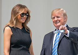 United States President Donald J. Trump shows off his special viewing glasses as he prepares to look at the partial eclipse of the sun from the Blue Room Balcony of the White House in Washington, DC on Monday, August 21, 2017.  First lady Melania Trump looks on at left.<br /> Credit: Ron Sachs / CNP