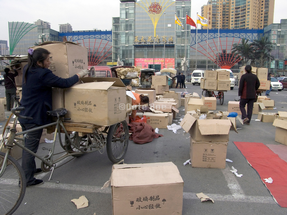 woman wrapping her goods on to her bicycle cart after a market day Beijing China