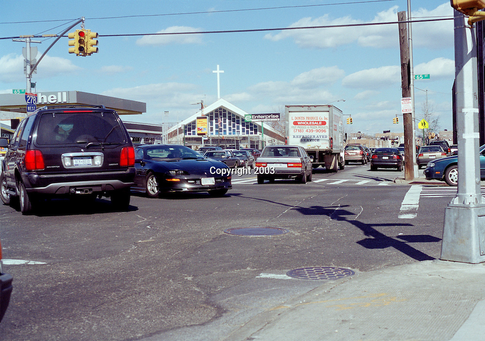 Congested Traffic intersection will crucifix and hell sign in Brooklyn, New York.