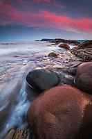 Colorful clouds light up at sunset along the rocky coastline of Cape Breton island, Nova Scotia, Canada