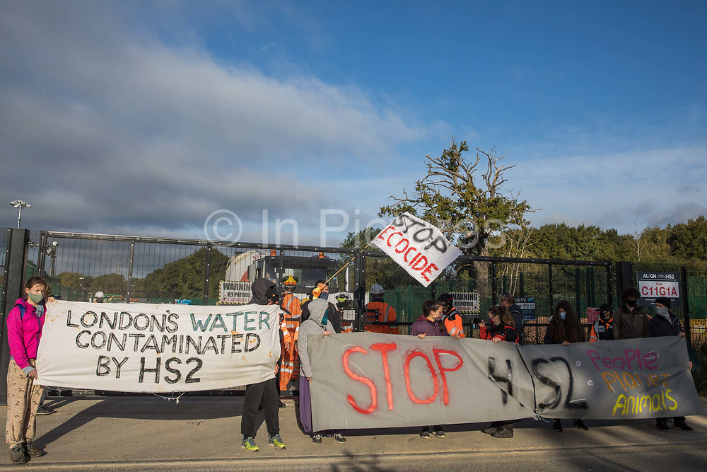 Environmental activists from HS2 Rebellion stand holding banners to block a gate providing access to a site for the HS2 high-speed rail link on 12 September 2020 in Harefield, United Kingdom. Anti-HS2 activists continue to try to prevent or delay works on the controversial £106bn HS2 high-speed rail link in the Colne Valley where thousands of trees have already been felled.