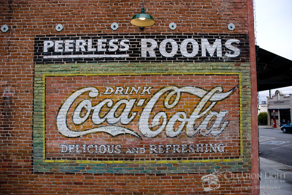 The railroad district of Ashland, Oregon still has intact many aspects of when the city was much younger including signs and buildings.  Advertising has changed since this sign was painted from the influence of the automobile and television.