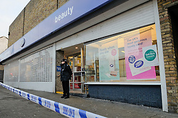 © under license to London News Pictures. 2010.12.13. Police guard the entrance to the store. A Man has been shot during a planned police operation in Eltham. Police attended Boots in Eltham High Street at 7am this morning (December 13) as part of a pre planned armed operation. During the operation a police firearm was discharged and a man received a gunshot wound. He was taken to hospital and his injuries are not thought to be life threatening. The man along with four others has been arrested. The bus stop in front of Boots is cornered off by police tape and a window of the store is cracked. Picture credit should read Grant Falvey/London News Pictures...