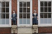 The two figures overlook the exterior of St. Mary Rotherhithe, the 15th century free school founded Peter and Robert Hill in 1613 in Rotherhithe, on 17th January 2020, in London, England.