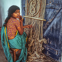 A young woman weaves macrame to sell in Dhaka, Bangladesh.