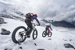 Couple riding electric fatbikes on snowcapped mountain, Passo di Stelvio, Lombardy, Italy