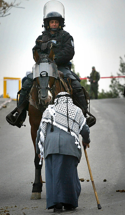 A Muslim man passes by horseman police officer guarding the Muslim worshippers praying in east Jerusalem, being concerned for clashes as a response for Israeli renovation work at a disputed holy site in Old City Feb. 10, 2007. Photo by Michal Fattal/Flash90.