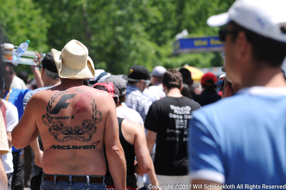 A fan with Formula 1 and McLaren tattoos walks through the concessions at the 2011 Formula 1 Canadian Grand Prix, Montral, QC. The tattoo includes dates (clockwise from bottom left) for Juan Manuel Fangio, Gilles Villeneuve, David Coulthard, Mika Häkkinen, Mario Andretti and Bruce McLaren.
