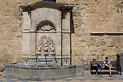 Resting travellers and fountains at the foot of the tall walls of the Archbishops Palace, on 23rd May, 2017, in Narbonne, Languedoc-Rousillon, south of France.