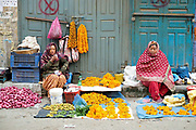 Women vendors selling vegetables and marigolds for temple offerings at the early morning market on the streets of Patan, Nepal.