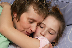 Single parent hugging her young daughter goodnight,