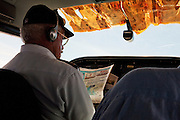 A pilot reads the day's paper as he flies a small, light aircraft towards Canaima National Park in Venezuela