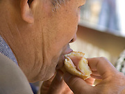 elderly man eating a sandwich
