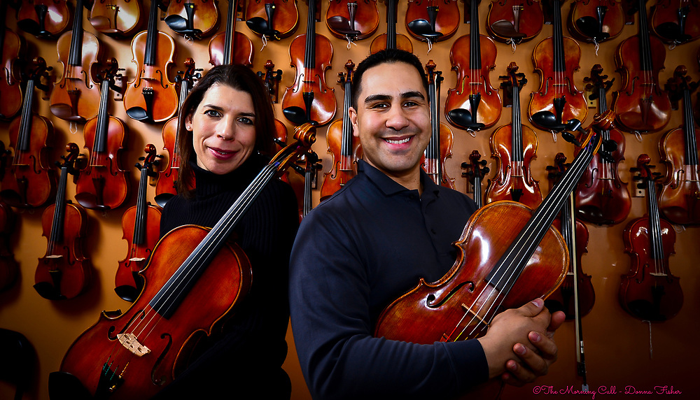 Jen and Mike Montero hold violas while their violins hang on the wall behind them in their Emmaus, Pa. shop. <br /> - Photography by Donna Fisher<br /> - ©2020 - Donna Fisher Photography, LLC <br /> - donnafisherphoto.com