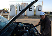With more than 24 hours of driving behind him, Cesar Marquina Corona looks upon the Texas countryside with weary eyes as he checks the engine on his Jeep and refuels the tank. Like thousands of other immigrant workers in Jackson Hole, Corona heads home after his visa expires, to the state of Tlaxcala, Mexico.