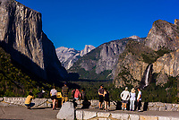 Tourists take in the iconic view of the Yosemite Valley (with El Capitan on left, Half Dome center and Bridalveil Fall on right) from Tunnel View, Yosemite National Park, California USA.