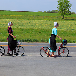 Gordonville, PA / USA - May 9, 2018: Two Amish women use bike scooters for transportation along a rural road in Lancaster County.