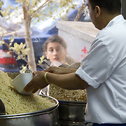 A passing woman catches a koshary chef's eye as he prepares food for the masses. During the Egyptian revolution, he would frequently work till 3 am to keep Tahrir Square protesters fed.