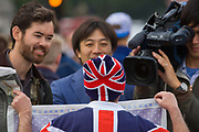 An Asian tv crew interview a royalist during celebrations of the Queen's record of years as monarch. Holding up a cloth with a royal theme, he shows the foreign broadcasters his colours, telling them of his love for the royal family and the British monarchy. The reporters seem to enjoy his tales of attending every royal event and celebration - a well-known character on the calendar whenever a procession, a birth or anniversary is celebrated.