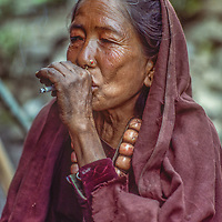 A Nepali woman smokes a cigarette cupped in her hand so that her lips will not pollute it.