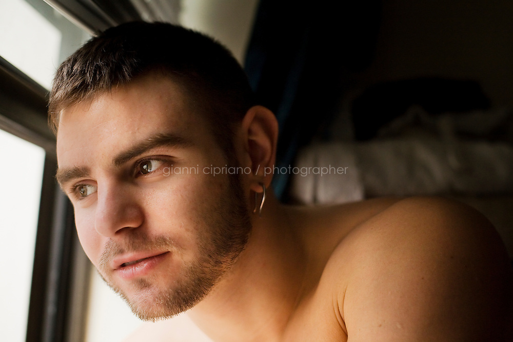 """11 December, 2008. New York, NY. Daniel Alexander Osach (or Dan Alex), 24, is here at the window of his apartment in the Upper East Side after taking a shower. Dan Osach is a gay Go-Go dancer who grew up in New Haven, CT, and moved to New York a year ago. During the day he works for Christopher Hyland, Inc., a high-end fabrics purveyor. At night, he works as a Go-Go dancer in gay and women clubs around New York City. """"My life is work, gym, dance and sleep"""", Daniela says. Dan has a bachelor in English and majored in Poetry and Economics. After graduation in 2006 he worked as a store manager in a mall for 4 months in Connecticut. Tired and depressed of his job, he went to Florida to relax and then came to New York a year ago. He usually dances at """"The Cock"""", a  East Village gay bar. """"The Cock is not an institution. It's a landmark"""" Daniel says. Daniel aspires to become maybe a teacher or to work for a travel magazine. """"What I would really love to do is to live my life laying down at the beach and reading poetry""""<br /> <br /> ©2008 Gianni Cipriano for The New York Times<br /> cell. +1 646 465 2168 (USA)<br /> cell. +1 328 567 7923 (Italy)<br /> gianni@giannicipriano.com<br /> www.giannicipriano.com"""