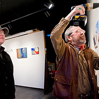 020613       Cable Hoover<br /> <br /> Erin Bulow, left, gets a hand from gallery owner Milan Sklenar to hang his show at Crashing Thunder Gallery in Gallup Wednesday.